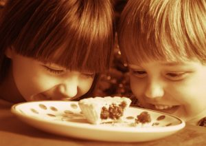 Two children looking at half a cookie