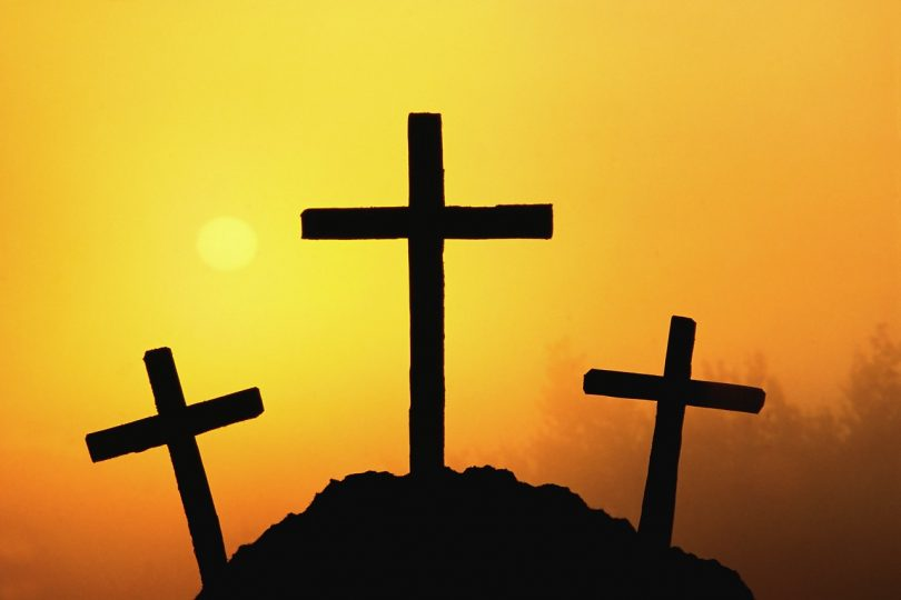 Three crosses on a hill in sunset